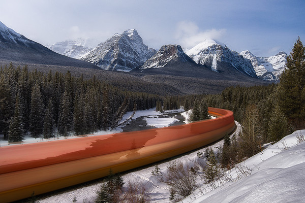 A long exposure shot of Morant's Curve while a train passes by - Banff