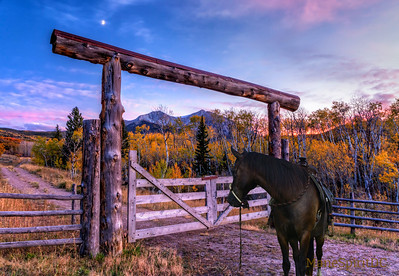 An entry gate to a ranch frames Mount Sopris at sunset near Carbondale, Colorado