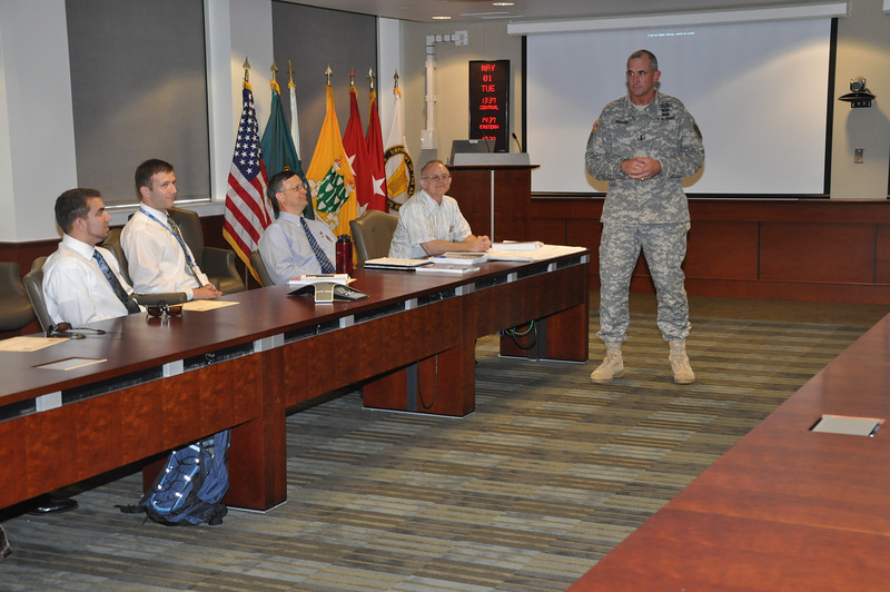 On 1 May 2012, MG Brown presents coins in recognition of excellence at the Wood Conference Room in McGinnis-Wickham Hall to engineering students from UGA and Auburn for their work designing environmentally-friendly maneuver trails and sedimentation control plans in the Good Hope training area. Photo by 2LT Duncan Michel, 316 CAV BDE