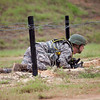 A soldier low crawls under barbed wire with his M4 Assault Rifle during the Best Warrior Competition, July 31, 2012 at Fort Benning, Ga. National Guardsmen competed for the title of NCO of the Year and Soldier of the Year for the National Guard. (US Army Photos by Ashley Cross)