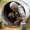 A National Guardsman maneuvers out of a tunnel in full kit during the Stress Shoot portion of the Best Warrior Competition, July 31, 2012 at Fort Benning, Ga. Stress shoots require soldiers to fire from the prone, kneeling and standing positions after moving through physically challenging events. (US Army Photo by Ashley Cross)
