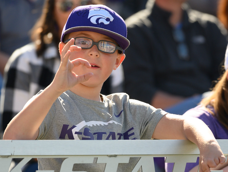 Eagerly watching the game over the edge of the stadium barrier, a young passionate fan wears a signed K-State hat. KSU and TCU faced off at Bill Snyder Family Stadium on Oct 19, 2019. The Wildcats defeated the Horned Frogs 24-17. (Dylan Connell | Collegian Media Group)