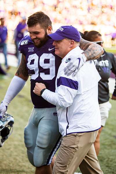 Senior defensive tackle Trey Dishon celebrates with head coach Chris Klieman while running off the field after winning their football game against TCU at Bill Snyder Family Stadium on Oct. 19, 2019. The Wildcats took the Horned Frogs 24-17. (Logan Wassall | Collegian Media Group)