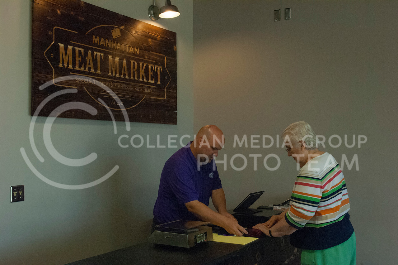 Dustin Downie assists a customer at the Manhattan Meat Market in Manhattan, Kan. on June 23, 2017. The Manhattan Meat Market is a local specialty meats and artisan butcher shop. (Justin Wright | The Collegian)