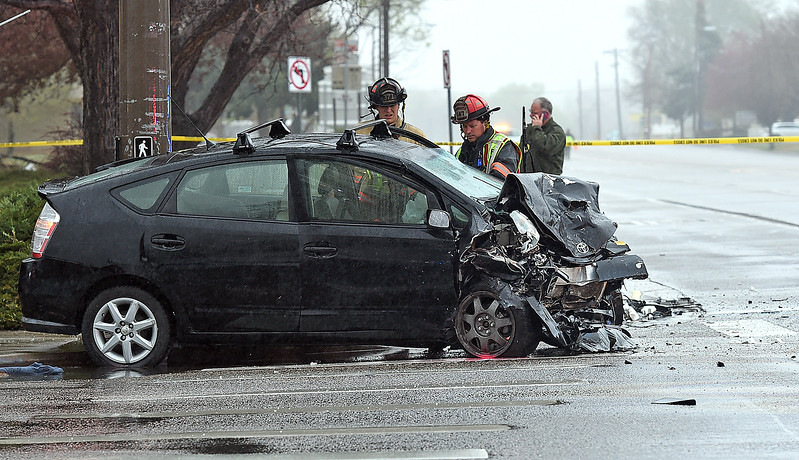 Loveland Police and Loveland Fire Rescue Authority work the scene of a crash Friday, March 31, 2017, at Eisenhower Boulevard and Wilson Avenue in west Loveland. Police were pursuing Adam Fulford, who was driving the black Toyota Prius, as part of a manhunt that started Thursday night.  (Photo by Jenny Sparks/Loveland Reporter-Herald)