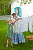 Girls hanging laundry on the clothes line at the Mennonite Heritage Village in Steinbach, Manitoba, Canada.