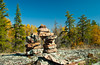 An inukshuk with fall foliage color in the Whiteshell Provincial Park, Manitoba, Canada.