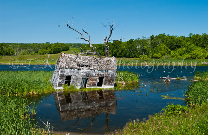 Abandoned home building in a flooded low lying area east of Riding Mountain National Park, Manitoba Canada.
