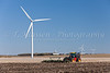 Farm tractor at work on a prairie field at the windfarm near St. Leon, Manitoba, Canada.