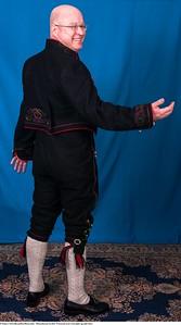 Mannsbunad fra Øst-Telemark med svart jakke og røde biser samt håndstrikkede strømper