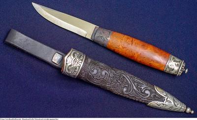 Mannsbunad fra Øst-Telemark med svart jakke og grønne biser. Telemark kniven er håndsmidd med utskåret slire av lær i gammelt  mønster.