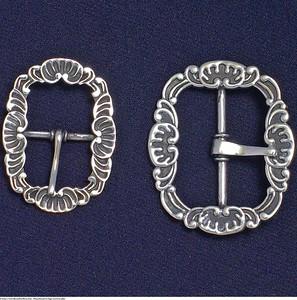 Mannsbunad fra Sogn med kvit jakke med knespenne i tradisjonelt Norsk bunadsmønster. Spennene er i bruk til en rekke Norske mannsbunader.