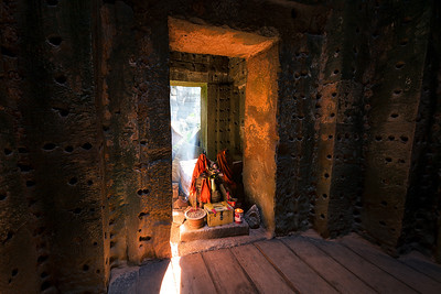A beam of light shine through and incense cloud at an ancient shrine in the angkor wat temple comples.  Siem Reap, Cambodia.  JumpingBorders.com