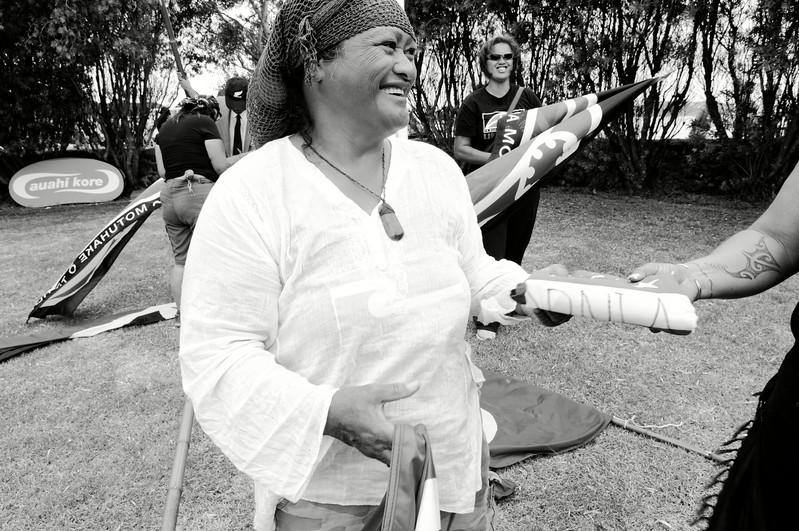 """Echange de drapeaux tribaux entre deux activistes maories à l'occasion des commémorations annuelles du Waitangi Day sur le site de la signature du traité de Waitangi. Le traité de Waitangi, signé le 6 février 1840 entre Britanniques et Maoris, est censé constituer l'acte """"fondateur"""" de la Nouvelle-Zélande. Mais pour de nombreux Maoris, il symbolise une forme de tromperie diplomatique et juridique ayant abouti à la confiscation de la majorité de leurs terres durant plus de 150 ans.<br /> Baie des Iles/Northland/Nouvelle-Zélande"""