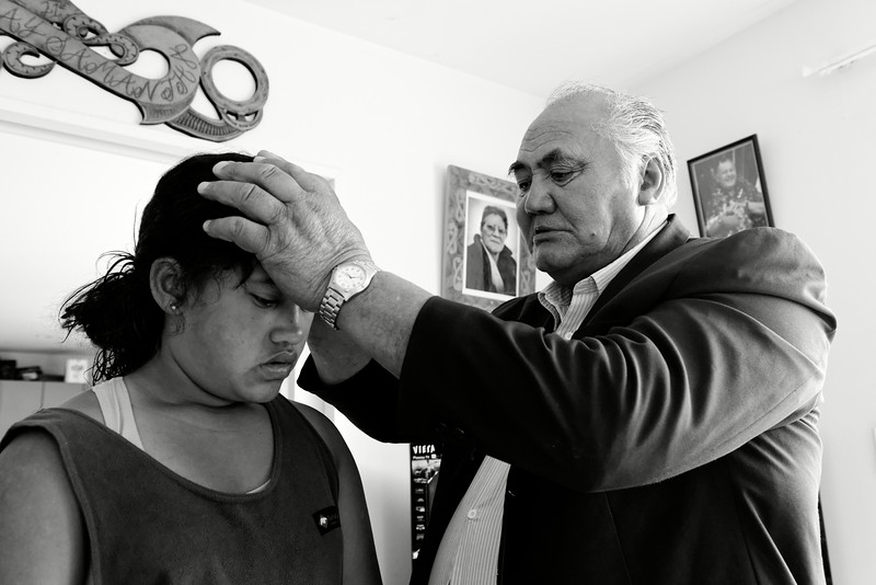 Le tohunga (médium/guérisseur traditionnel maori) John Te Rata Puke en train de soigner la jeune Tatiana Osborne (se plaignant de maux de gorge et maux de tête) par apposition des mains, dans sa maison de Kawhia. Depuis une dizaine d'années, les organismes de santé néo-zélandais financent des services de médecine traditionnelle maorie au sein de leurs centres de santé. Une vingtaine de services de ce type reçoivent des financements gouvernementaux. En outre, rongoa (la médecine traditionnelle maorie) est en train de trouver une reconnaissance à l'hôpital comme complément de la médecine conventionnelle.<br /> Waikato/Nouvelle-Zélande