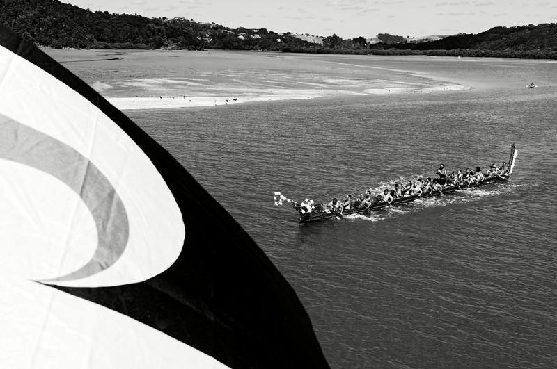 """Un waka (pirogue traditionnelle maorie) participant aux commémorations annuelles du Waitangi Day sur le site de la signature du traité de Waitangi (Tino rangatiratanga, le drapeau """"national"""" maori, au 1er plan). Le traité de Waitangi, signé le 6 février 1840 entre Britanniques et Maoris, est censé constituer l'acte """"fondateur"""" de la Nouvelle-Zélande. Mais pour de nombreux Maoris, il symbolise une forme de tromperie diplomatique et juridique ayant abouti à la confiscation de la majorité de leurs terres durant plus de 150 ans.<br /> Baie des Iles/Northland/Nouvelle-Zélande"""