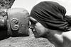 Le hongi est le salut traditionnel maori. Ce geste d'accueil, front contre front et nez contre nez, est censé permettre l'échange du souffle vital et, le cas échéant, faciliter l'intégration d'un visiteur au sein du groupe. Dans certains cas, comme avec ce jeune charpentier de marine de la Waka Building School, l'individu effectuant un hongi avec une divinité (sculptée ici à l'avant d'une grande pirogue) en retirera le renforcement de sa connexion spirituelle.<br /> Doubtless Bay/Northland/Nouvelle-Zélande