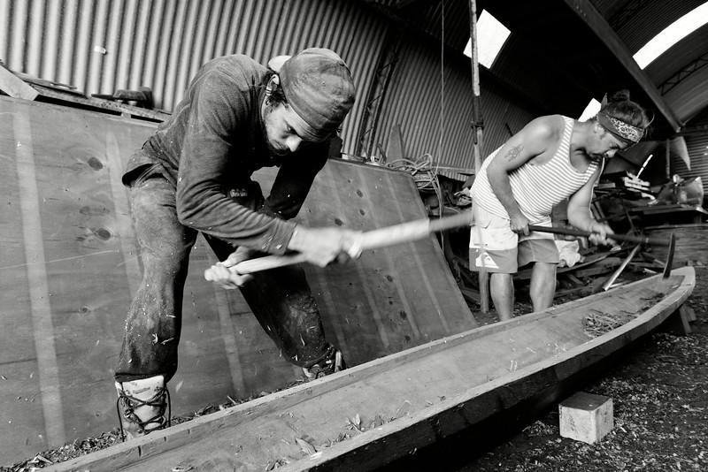 Jeunes charpentiers de marine maoris de la Waka Building School (Doubtless Bay) en train de construire un petit waka (pirogue traditionnelle maorie). Northland/Ile du Nord/Nouvelle-Zélande