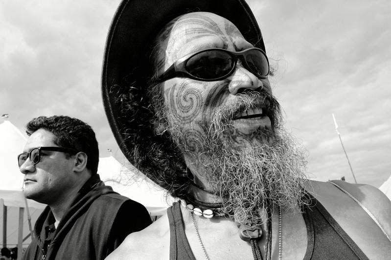 Le tatouage maori, appelé ta moko, était traditionnellement réalisé à l'aide de petits burins en os d'albatros trempés dans une encre végétale et martelés à coups de maillet (on utilise aujourd'hui des tatoueuses électriques). Il fonctionne comme une carte d'identité révélant la tribu, l'ascendance et le rang social. Le côté droit du visage est réservé à la famille paternelle alors que la gauche concerne la mère. Plus les motifs se développent sur le haut du front, plus l'homme est important. Ici, le portrait d'un Maori participant aux commémorations annuelles du Waitangi Day sur le site de la signature du traité de Waitangi. Baie des Iles/Northland/Ile du Nord/Nouvelle-Zélande