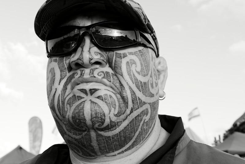 Le tatouage maori, appelé ta moko, était traditionnellement réalisé à l'aide de petits burins en os d'albatros trempés dans une encre végétale et martelés à coups de maillet (on utilise aujourd'hui des tatoueuses électriques). Il fonctionne comme une carte d'identité révélant la tribu, l'ascendance et le rang social. Le côté droit du visage est réservé à la famille paternelle alors que le gauche concerne la mère. Plus les motifs se développent sur le haut du front, plus l'homme est important. Ici, le portrait d'un Maori participant aux commémorations annuelles du Waitangi Day sur le site de la signature du traité de Waitangi.<br /> Baie des Iles/Northland/Nouvelle-Zélande
