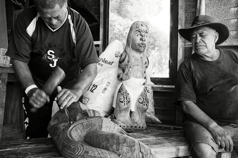 """La sculpture fait partie intégrante de l'identité maorie. Dans le bois, la nacre, l'os ou le pounamu, ce """"jade"""" de la Nouvelle-Zélande roulé par les torrents de montagne de l'Ile du Sud, les artistes maoris ont depuis des siècles sublimé la matière. Ici, le sculpteur tuhoe John Rua, observé par son ami Korotau Tamiana, réalise dans une bille de bois des forêts sacrées de Te Urewera, l'effigie d'une divinité.<br /> Ruatoki/Bay of Plenty/Nouvelle-Zélande"""