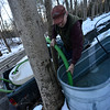 KRISTOPHER RADDER - BRATTLEBORO REFORMER<br /> Jerry Smith, of Deer Ridge Farm, in Guilford,  collects the sap that trickled into tubs.