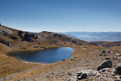 Having lunch at  mountain tarn with Lake Hawea in distance from Pisa Range, Otago, New Zealand