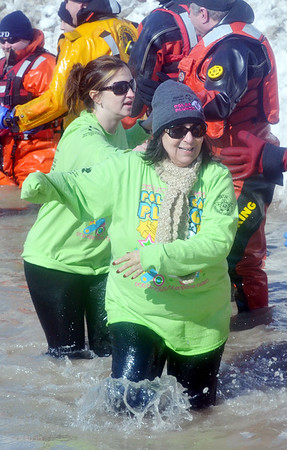 WARREN DILLAWAY / Star Beacon A PARTICIPANT in the  Polar Bear Plunge, held Saturday at Geneva State Park, prepares to slaps hands with a dive team member. The event raised an estimated $90,000 for Special Olympics Ohio.