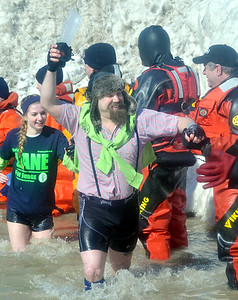 """WARREN DILLAWAY / Star Beacon JOE GALLAGHER of Erie carries an ice """"torch"""" during the Polar Bear Plunge held Saturday at Geneva State Park. The event raised an estimated $90,000 for Special Olympics Ohio."""
