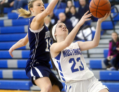 WARREN DILLAWAY / Star Beacon ABBY TRISKETT (23) of Grand Valley drives to the basket as Amanda Tishman of Rootstown tries to block the shot on Saturday at Grand Valley during a Division III sectional championship game.
