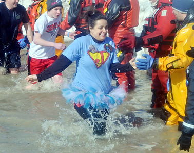 WARREN DILLAWAY / Star Beacon A TUTU clad participant in the  Polar Bear Plunge held Saturday at Geneva State Park slaps hands with a dive team member. The event raised an estimated $90,000 for Special Olympics Ohio.