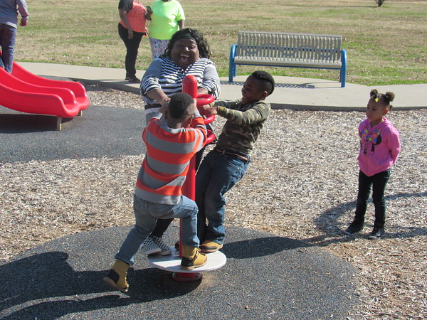 Staff photo by Cathy Spaulding<br /> Several families had fun Tuesday afternoon at Beckman Park. Charlene Troup joins the fun as she twirls with her sons, Antonio Walker, 6, left, and Aston Walker, 5, on a merry-go-round type pole. According to Muskogee's AccuWeather website, warmer temperatures, but cloudy skies are expected through the end of the school week.