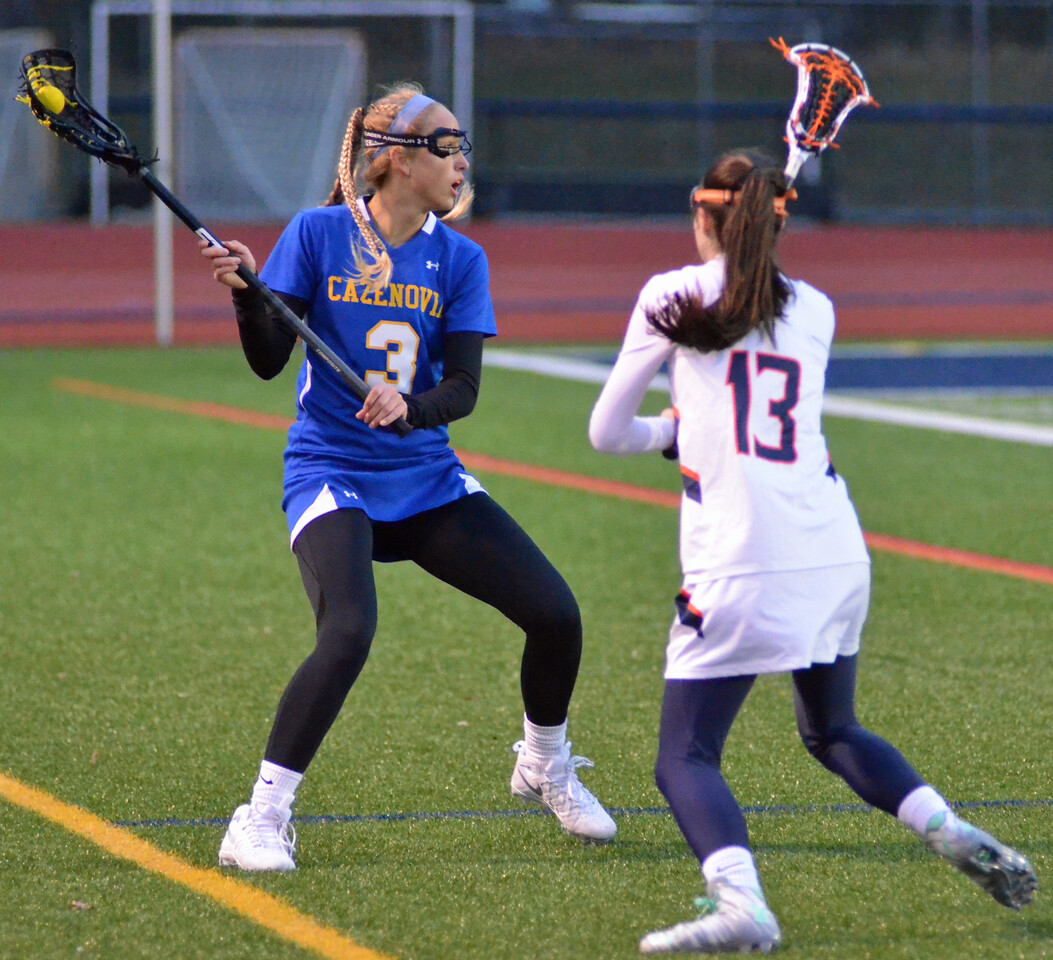 KYLE MENNIG - ONEIDA DAILY DISPATCH Cazenovia's Megan Henderson (3) looks to pass as Liverpool's Kate Salanger (13) defends during their game in Liverpool on Thursday, March 30, 2017.