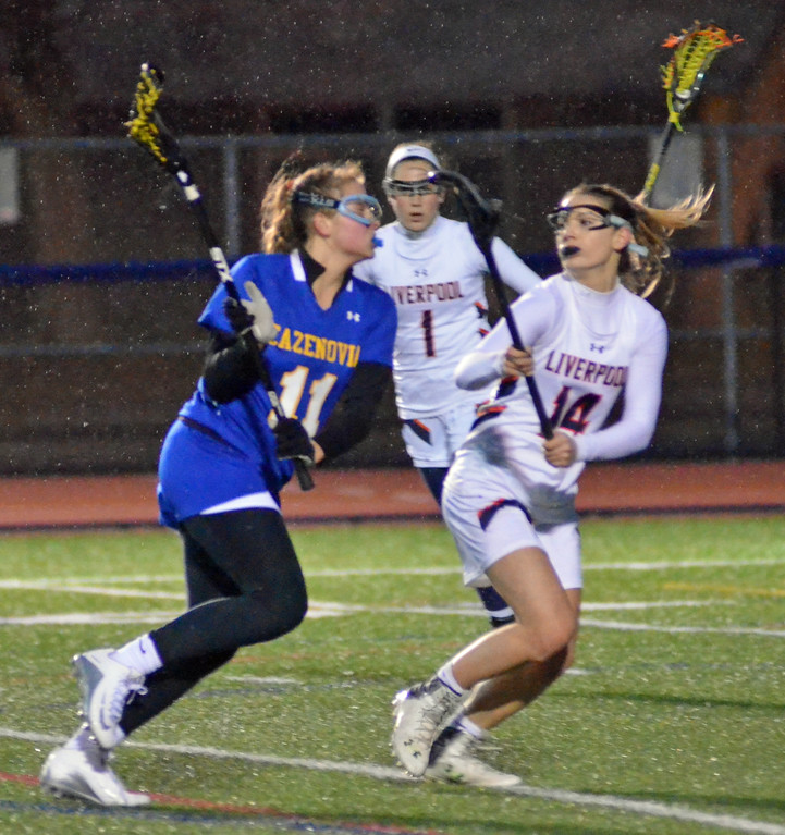. KYLE MENNIG - ONEIDA DAILY DISPATCH Cazenovia\'s Grace Rajkowski (11) takes the ball towards the goal as Liverpool\'s Maia Henry (14) defends during their game in Liverpool on Thursday, March 30, 2017.