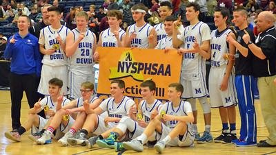 KYLE MENNIG - ONEIDA DAILY DISPATCH Madison players pose with the Section III championship banner after defeating McGraw in the Class D final in Syracuse on Sunday, March 5, 2017.