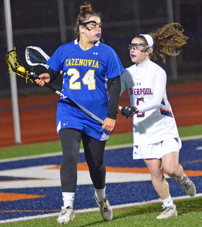 . KYLE MENNIG - ONEIDA DAILY DISPATCH Cazenovia\'s Chloe Willard (24) brings the ball out from behind the goal as Liverpools Leigha Johnson (5) defends during their game in Liverpool on Thursday, March 30, 2017.