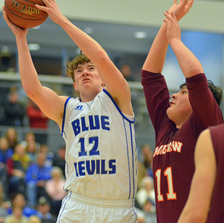. KYLE MENNIG - ONEIDA DAILY DISPATCH Madison\'s Jordan Crane puts up a shot inside as McGraw\'s David Smith (11) defends during the Section III Class D final in Syracuse on Sunday, March 5, 2017.
