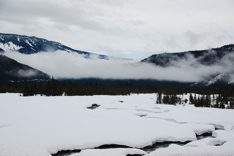In the Mount Hood NF, a stream cuts it's way through a snowy meadow while low clouds obscure the distant mountain ranges.
