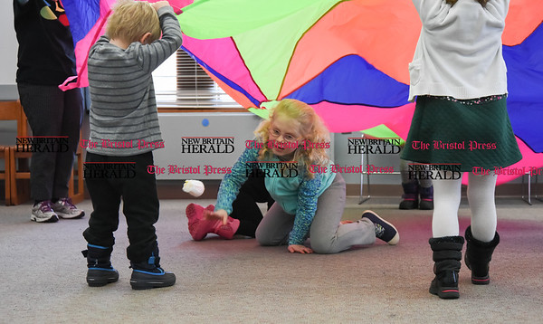031617 Wesley Bunnell | Staff Thursday's at the Berlin-Peck Library feature Bookworms which is a free program targeting children 3-5 years old. The program helps teach independence and a love of reading. 7 year old Sydelle Holland climbs under a parachute during a playtime exercise.