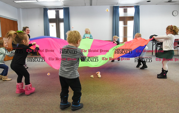 031617 Wesley Bunnell | Staff Thursday's at the Berlin-Peck Library feature Bookworms which is a free program targeting children 3-5 years old. The program helps teach independence and a love of reading. Using a parachute to pop popcorn are from left, 4 year old Carolina Foster, librarian Sarah Prattson, 3 year old Juliana Ginolfi, 3 year old Michael Beyer, 7 year old Sydelle Holland, 4 year old Rylin Holland, 4 year old Catherine Puzio and 4 year old Annabelle Meagher.