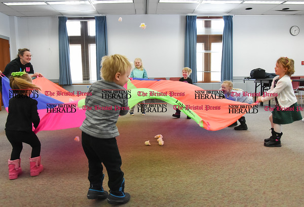 031617 Wesley Bunnell | Staff Thursday's at the Berlin-Peck Library feature Bookworms which is a free program targeting children 3-5 years old. The program helps teach independence and a love of reading. Using a parachute to pop popcorn are from left, librarian Sarah Prattson, 3 year old Juliana Ginolfi, 3 year old Michael Beyer, 7 year old Sydelle Holland, 4 year old Rylin Holland, 4 year old Catherine Puzio and 4 year old Annabelle Meagher.