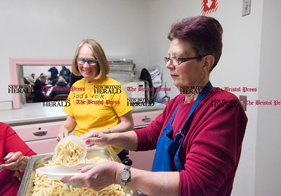 030817  Wesley Bunnell | Staff  First Lutheran Church in New Britain is running short of the money needed to hold their pasta supper as they have every Wednesday night to feed the homeless.  Nancy Peterson helps prepare a plate of pasta as Kris Fletcher waits to bring it to the window to be served.