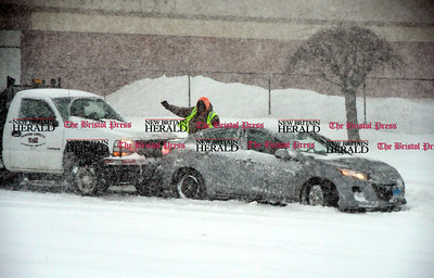 3/14/2017 Mike Orazzi | Staff A work truck pushes a stranded motorist on North Main Street in Bristol during Tuesday's snow storm.
