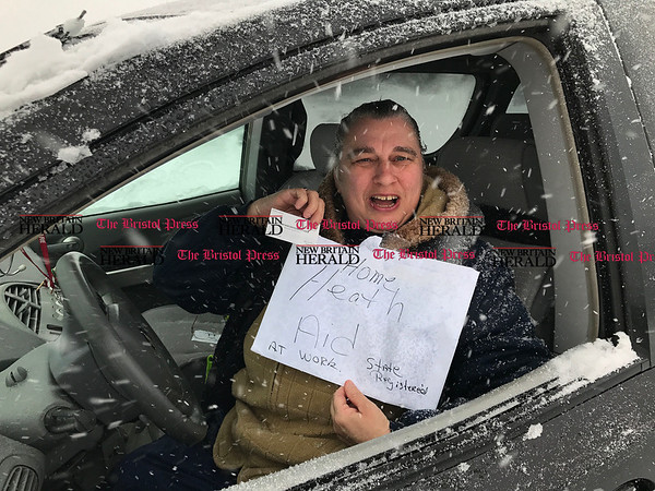 3/14/2017 Mike Orazzi | Staff Home health care worker Nancy Ross holds up a sign while out in Bristol during Tuesday's snow storm.