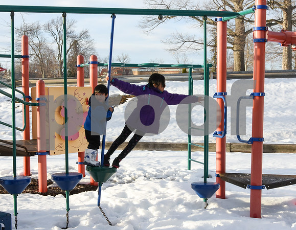 032017 Wesley Bunnell | Staff Jayline Arenas, age 9, reaches across for the next obstacle while Josue Arenas , age 3, waits for help on a playscape in Walnut Hill Park on the first day of Spring Mar. 20, 2017.