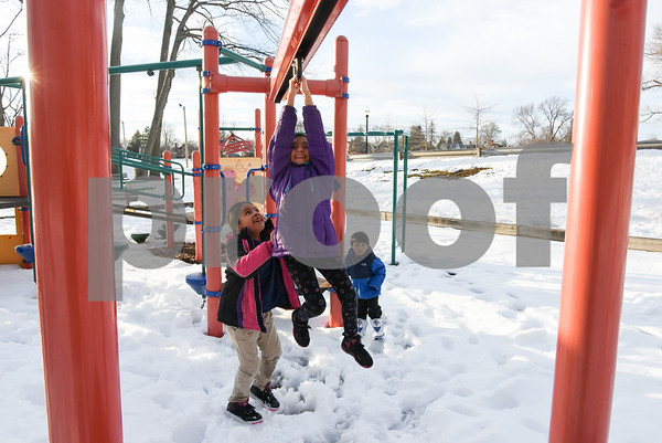 032017 Wesley Bunnell | Staff Jayline Arenas, age 9, holds on tight as she slides across to another side of a playscape with a push from Mairely Guerrero,age 7, in Walnut Hill Park on the first day of Spring Mar. 20, 2017. Josue Arenas, age 3, looks on in the background.