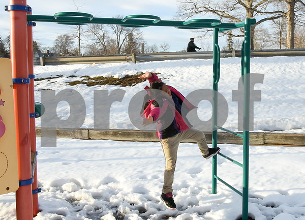 032017 Wesley Bunnell | Staff Mairely Guerrero, age 7, lets go as she works her way across the monkey bars on in Walnut Hill Park on the first day of Spring Mar. 20, 2017.
