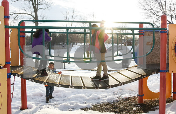 032017 Wesley Bunnell | Staff Jesus Balbuena, age 6, throws a snowball at Jayline Arnas, age 9, as she jumps up and down on a playscape walkway in Walnut Hill Park along with Mairely Guerrero, age 7, on the first day of spring Mar. 20, 2017.
