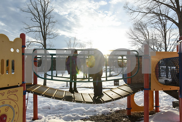 032017 Wesley Bunnell | Staff Silhouetted as they jump up and down on a playscape bridge in Walnut Hill Park Jayline Arenas, age 9, and Adrian Guerrero, age 7.
