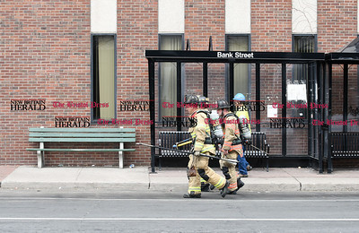032117  Wesley Bunnell | Staff  The New Britain Fire Department investigated a possible gas leak at 267 Main St on March 21, 2017. Fire and gas workers walk down Bank St towards the front of the building.